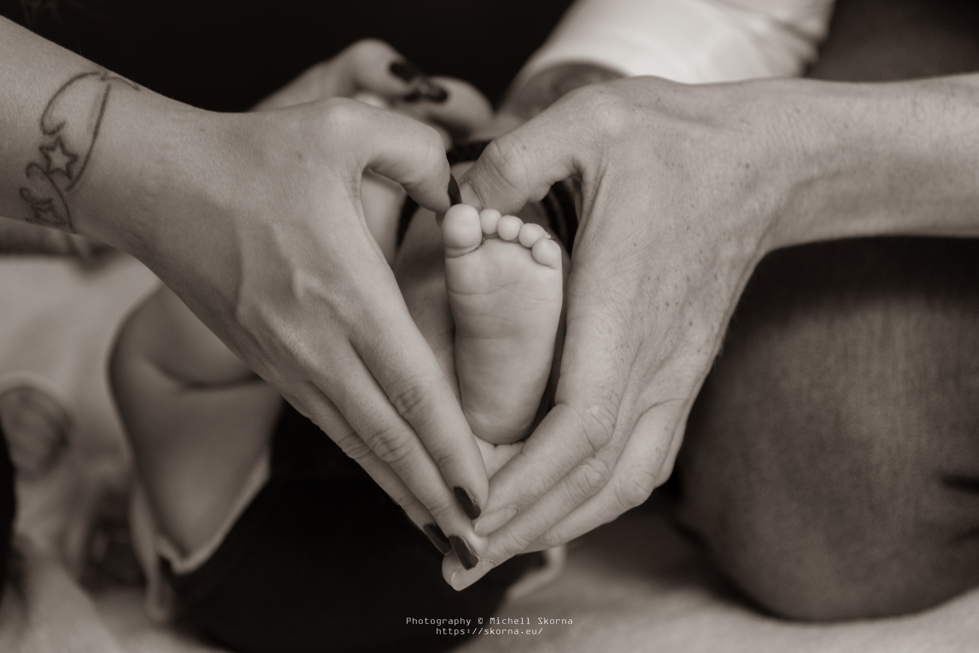 Couple holding the feet of their newborn baby in their hands. Their hands are forming a heart.